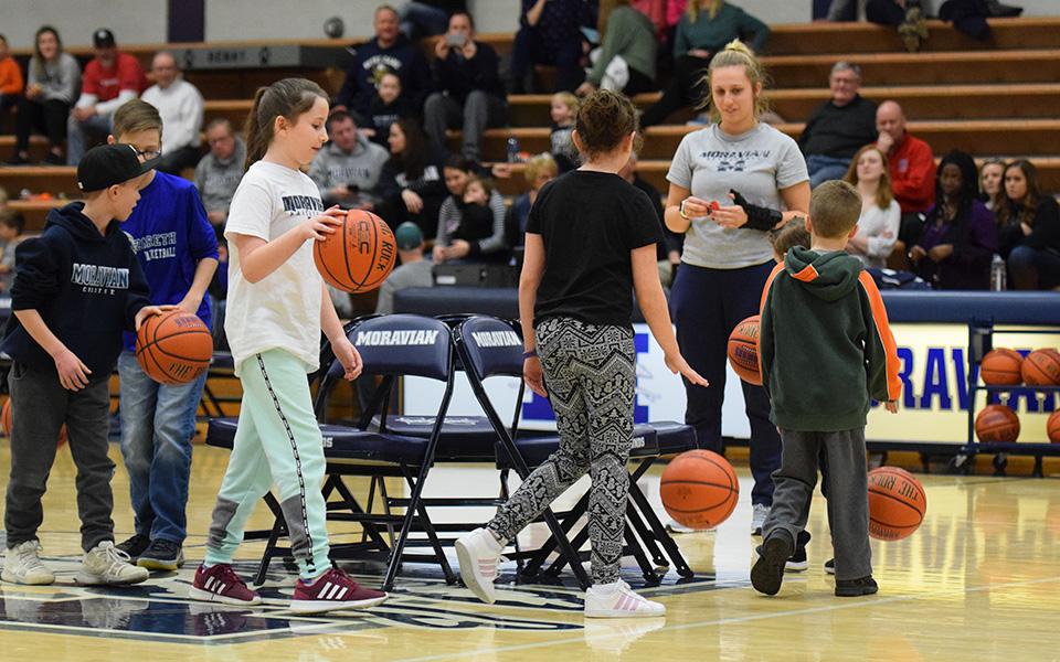 Kids play musical basketball chairs during the 2019 Moravian Take A Kid to the Game Day.