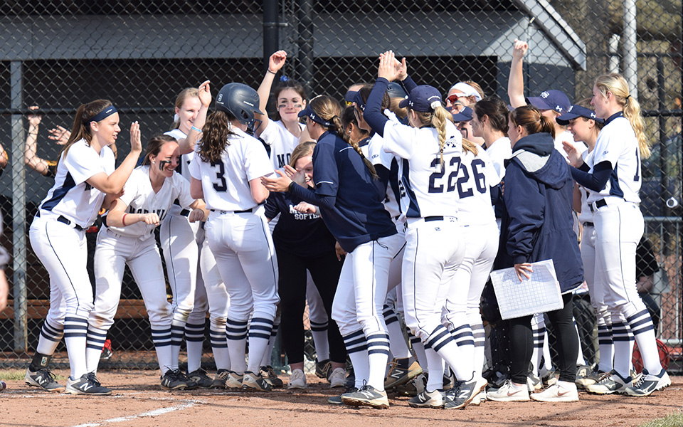 The Greyhounds greet junior Lauren Goetz at home after one of her two home runs in the 2019 home opener versus Gwynedd Mercy University at Blue & Grey Field.
