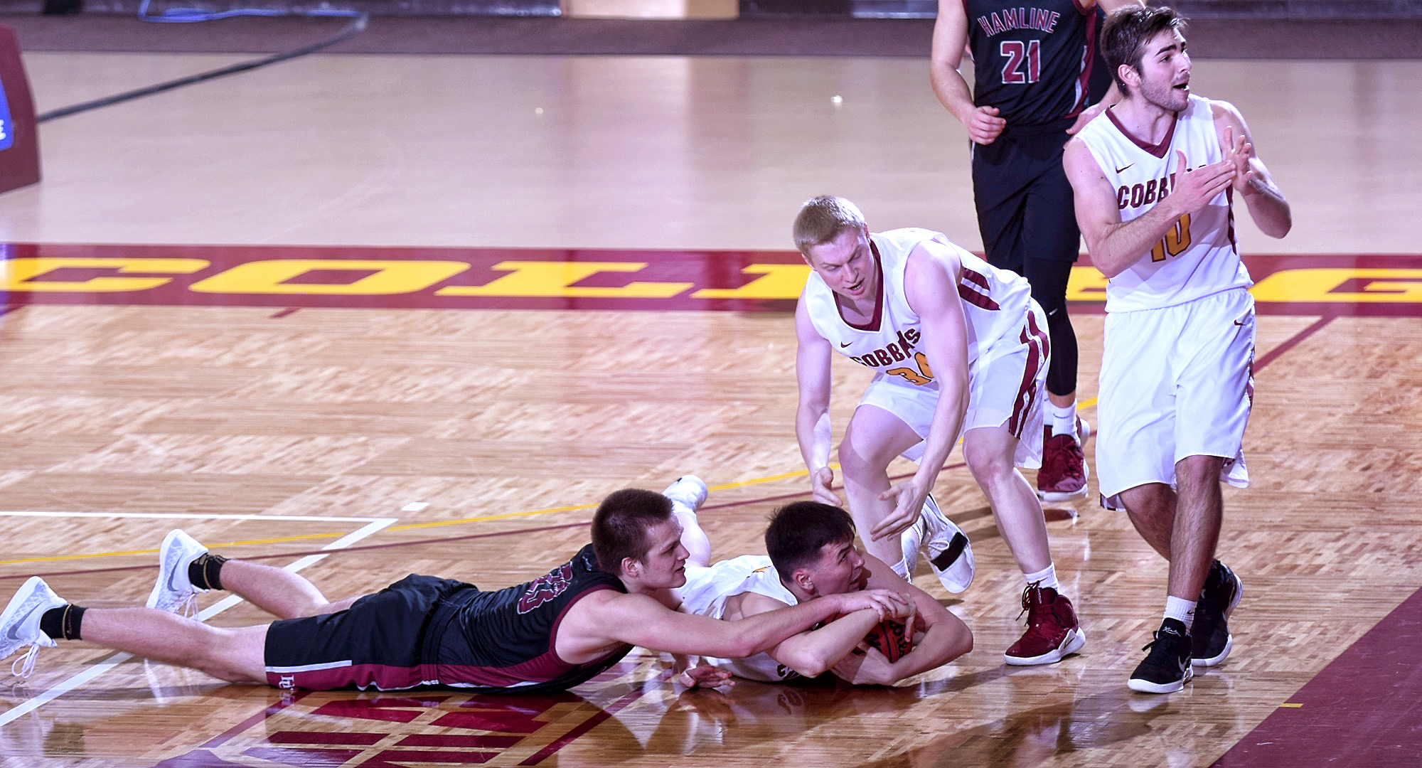Senior Jordan Davis dives on the floor to grab the ball as teammate Tommy Schyma calls for timeout late in the second half of the Cobbers' 68-62 win over Hamline.