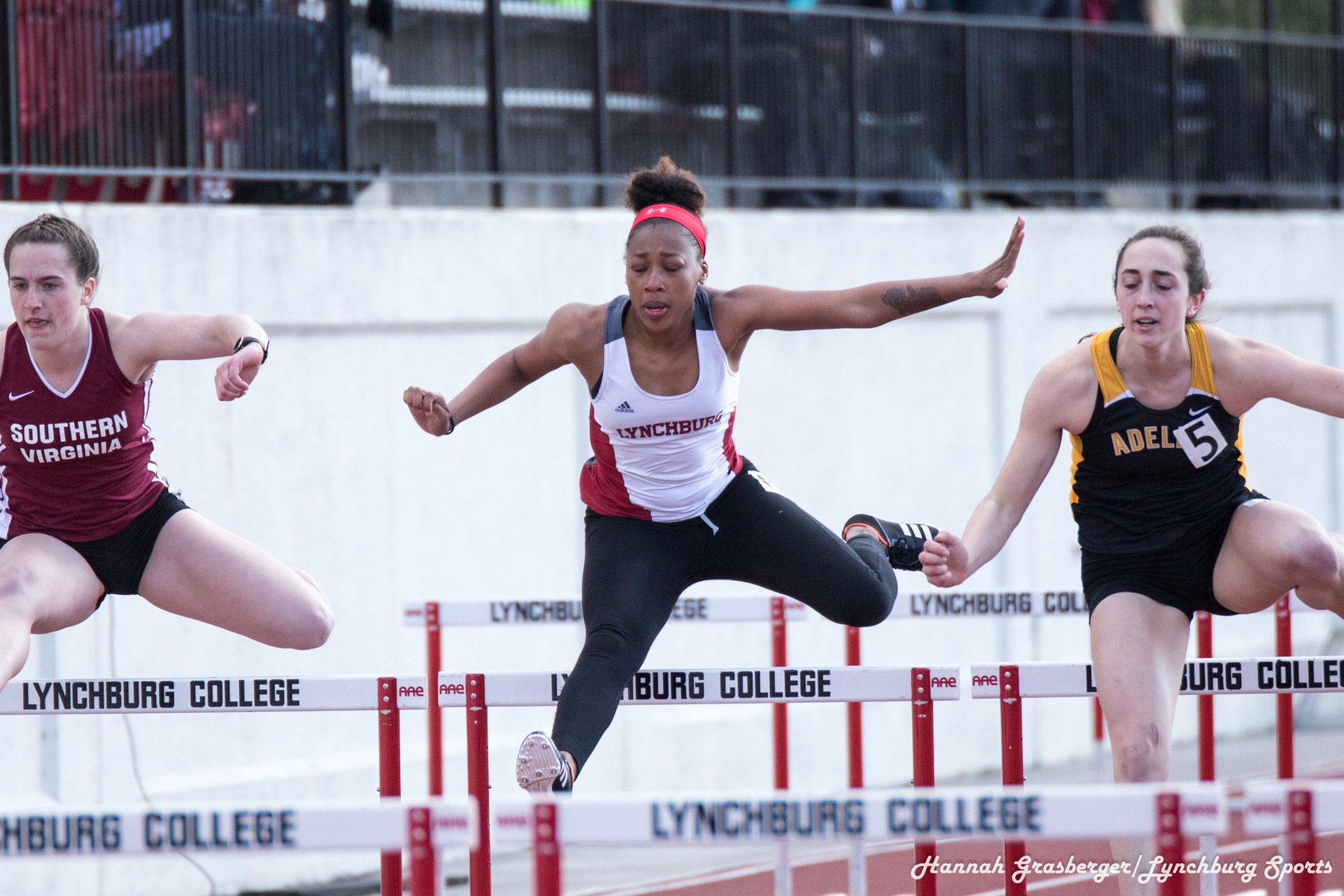 LaMaya Lacy jumping a hurdle in a race