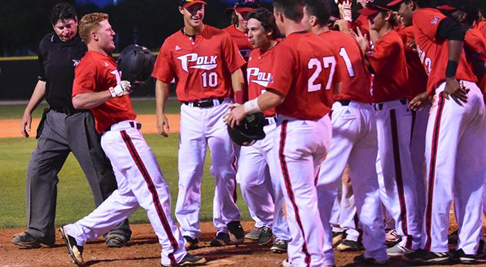 The Eagles congratulate Cole Warken (left) at home plate after his game-winning three-run home run. (Photo by Tom Hagerty, Polk State.)