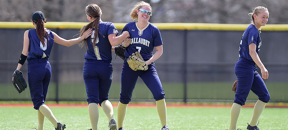Gallaudet softball players gather in the outfield. In the middle is #7 Hannah Neild. #5 Kelsey Hudson gives Neild a high-five while #0 Hailey Henshaw (left) and #3 Sabina Shysh (right) walk away in opposite directions.