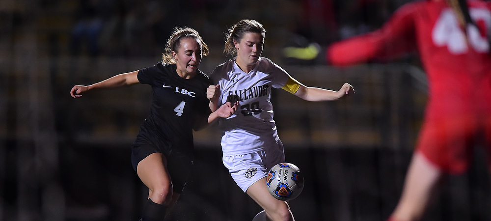 Gallaudet women's soccer player Hannah Neild runs by a Lancaster Bible defender during a night game at Gallaudet.