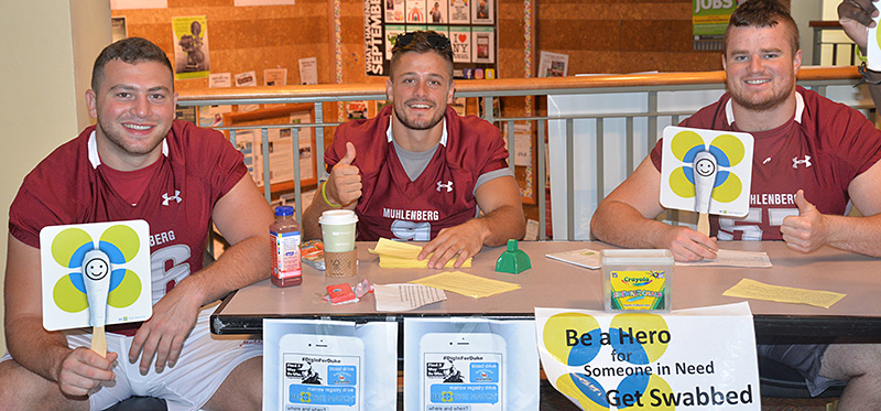Muhlenberg players urge people to get their cheeks swabbed to see if they are a match for anyone in need on the bone marrow registry.