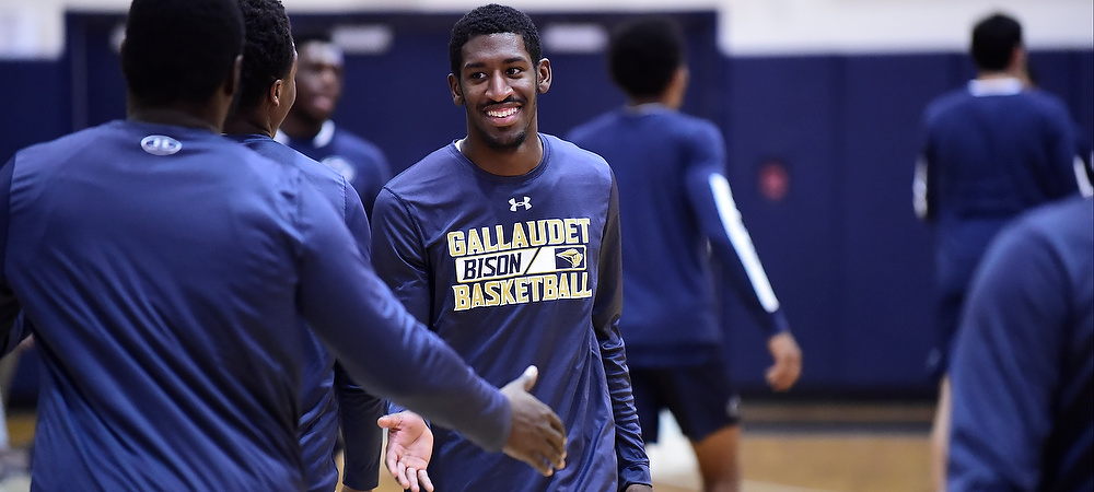 Gallaudet men's basketball guard Corey Smith smiles and slaps five with a teammate during warm ups