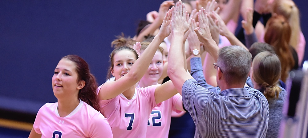 Members of the Gallaudet women's volleyball team give each other high fives after a win.