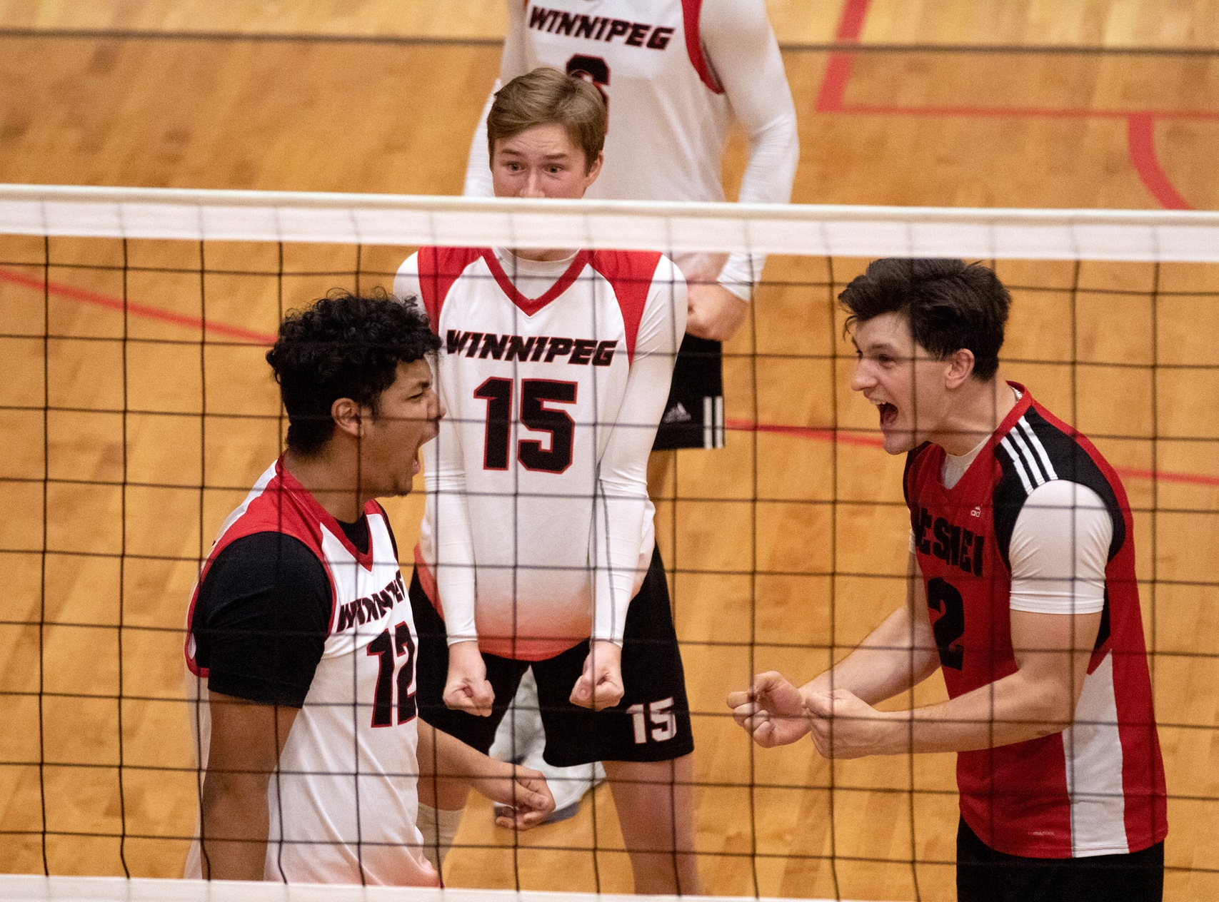 Kalen Reyes (left), Ben Traa (centre) and Darian Picklyk celebrate Reyes' first career kill during a Wesmen men's volleyball win over the Dalhousie Tigers, Thursday, Oct. 3, 2019. (David Larkins/Wesmen Athletics)