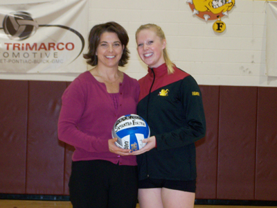 Samantha Fordyce receives a ceremonial 2,000 career assists ball from head coach Tia Brandel-Wilhelm.