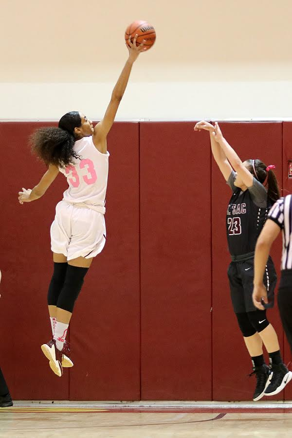 Kailyn Gideon goes up high to block the 3-point shot attempt of Mt. SAC's Maddeline Dopplick Wednesday night. The Lancers wore their special Coaches v. Cancer pink/white uniforms in the defeat, photo by Richard Quinton.