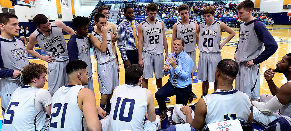 Gallaudet men's basketball huddle during a timeout. Coach Kevin Kovacs (middle) signs to his team instructions. Five players sit on the bench while the remainder of the team stands behind the coach.