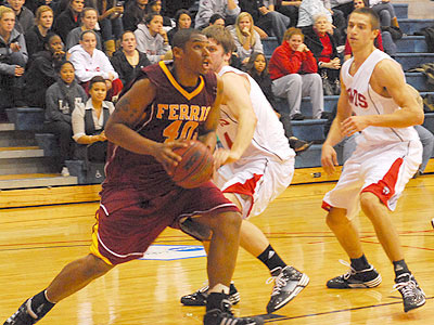 Justin Keenan drives to the basket in the season opener at Lewis (Photo by Rob Bentley)