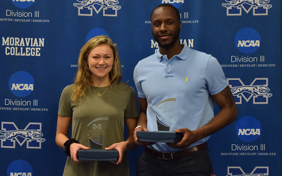 Juniors Karlie Brogan and John Hargraves accept the awards for the most community service hours for the men's and women's basketball teams.