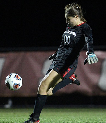 Red Devil goalkeeper Carli Boyer looks to clear the ball