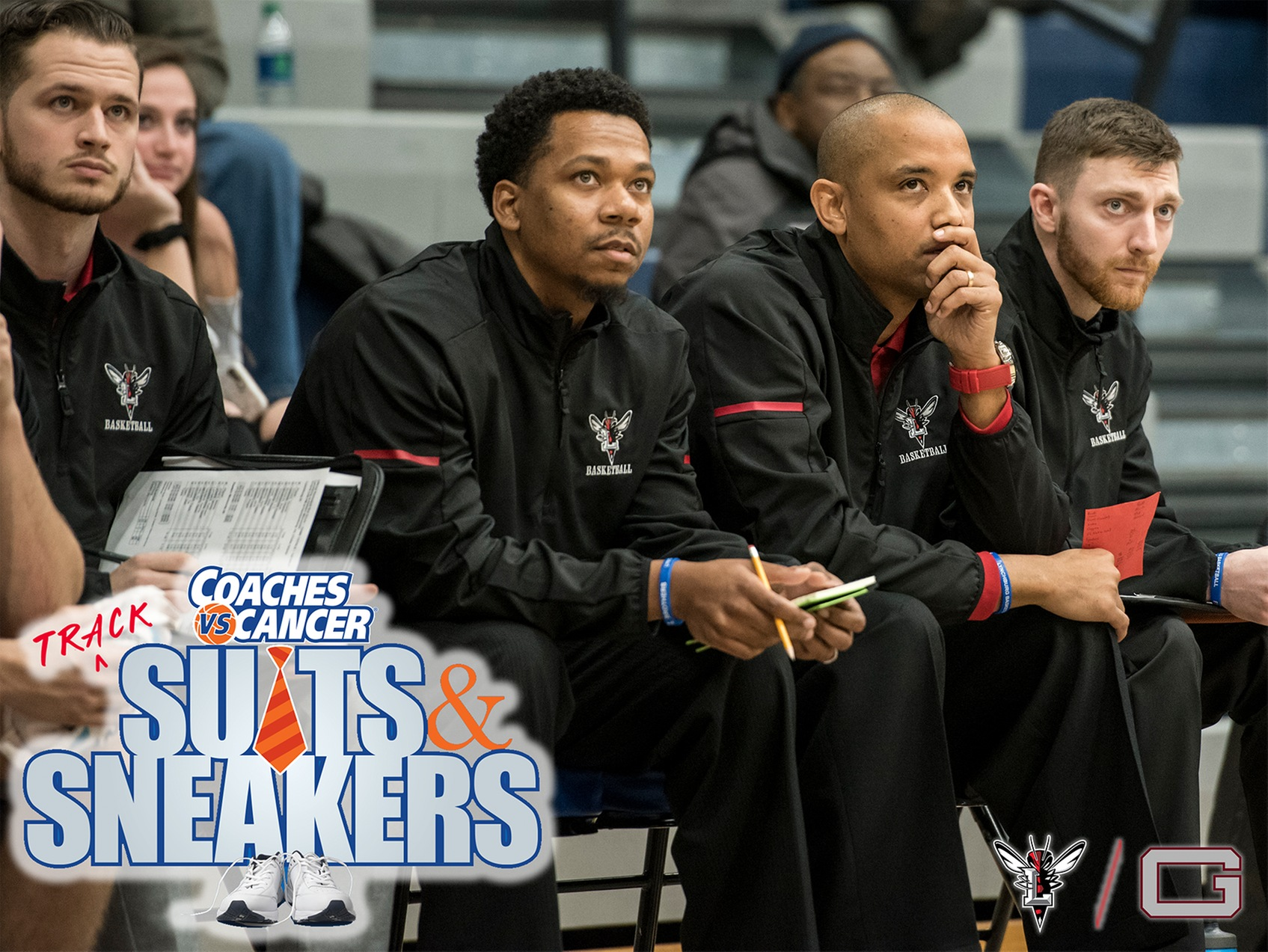 Lynchburg men's basketball coaches sit on the bench watching a game