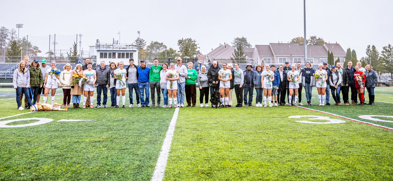 Image of all nine Endicott women's soccer seniors and their families on the field for the pre-game celebration.
