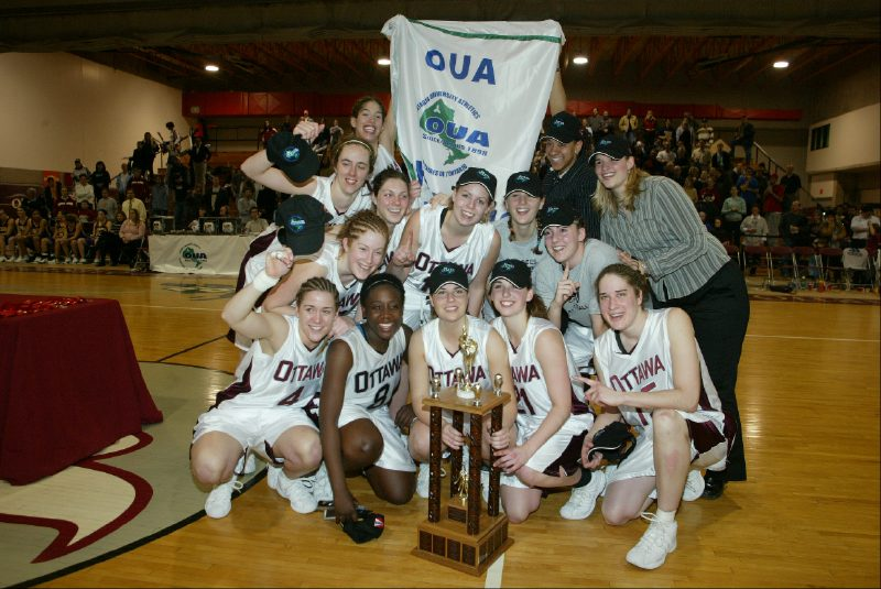 Team with OUA banner and trophy at Montpetit Hall.