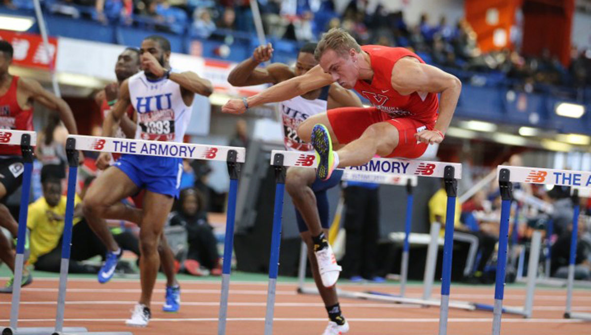 Chad Zallow jumps over a hurdle