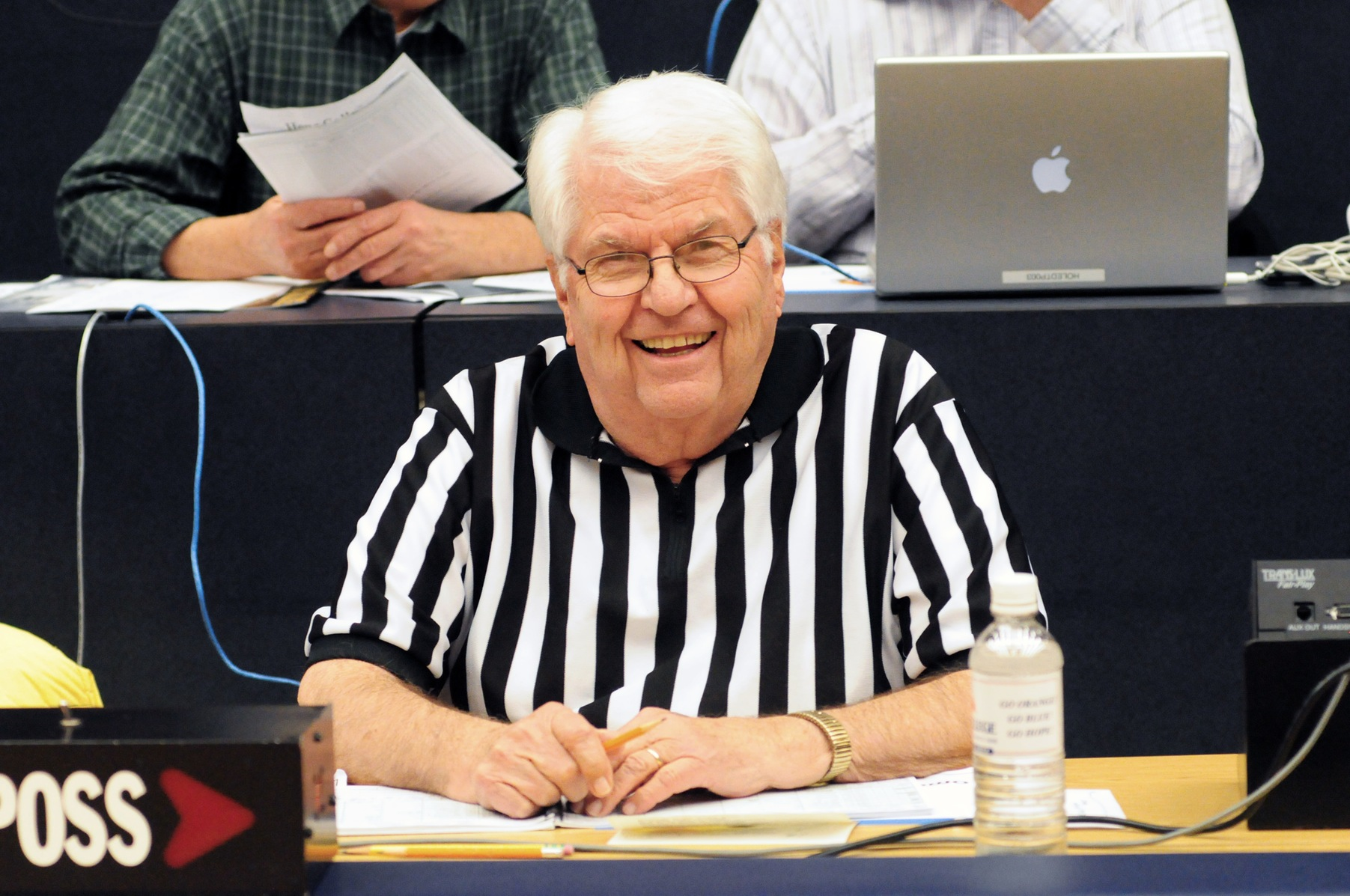 "Norman ""Bunko"" Japinga working the scorer's table at a basketball game while wearing an official's black-and-white shirt"