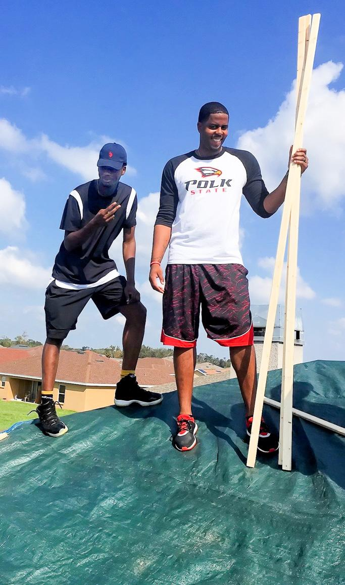 Veron Kalonji and Head Coach Brandon Giles help make temporary repairs on a roof damaged by Hurricane Irma.