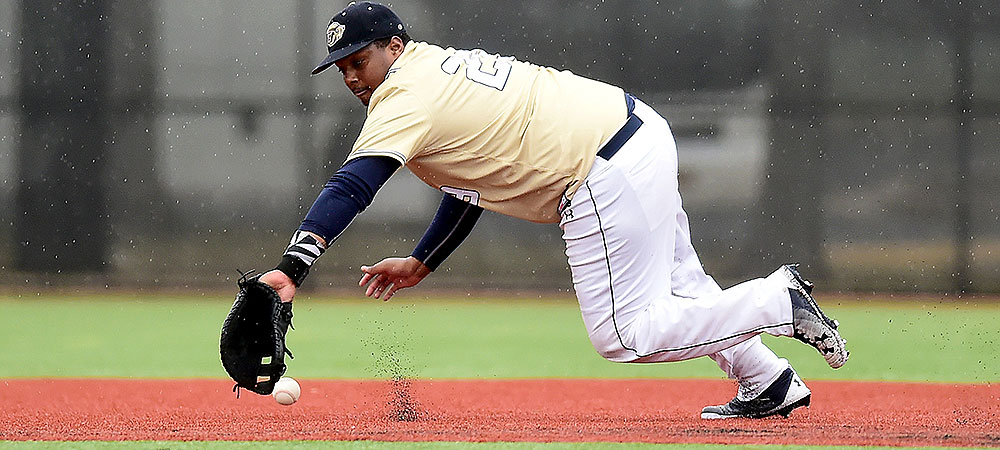 GU's Justin Strong makes a dive in the infield trying to get a baseball hit by him in the rain.