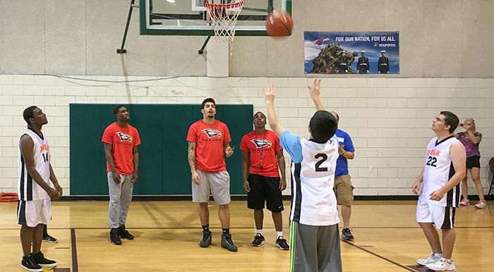Eagle players Kahleek Bakare-Whyte, Elijah Cottrell, and Ron Lubin work with Special Olympians during skills competition.