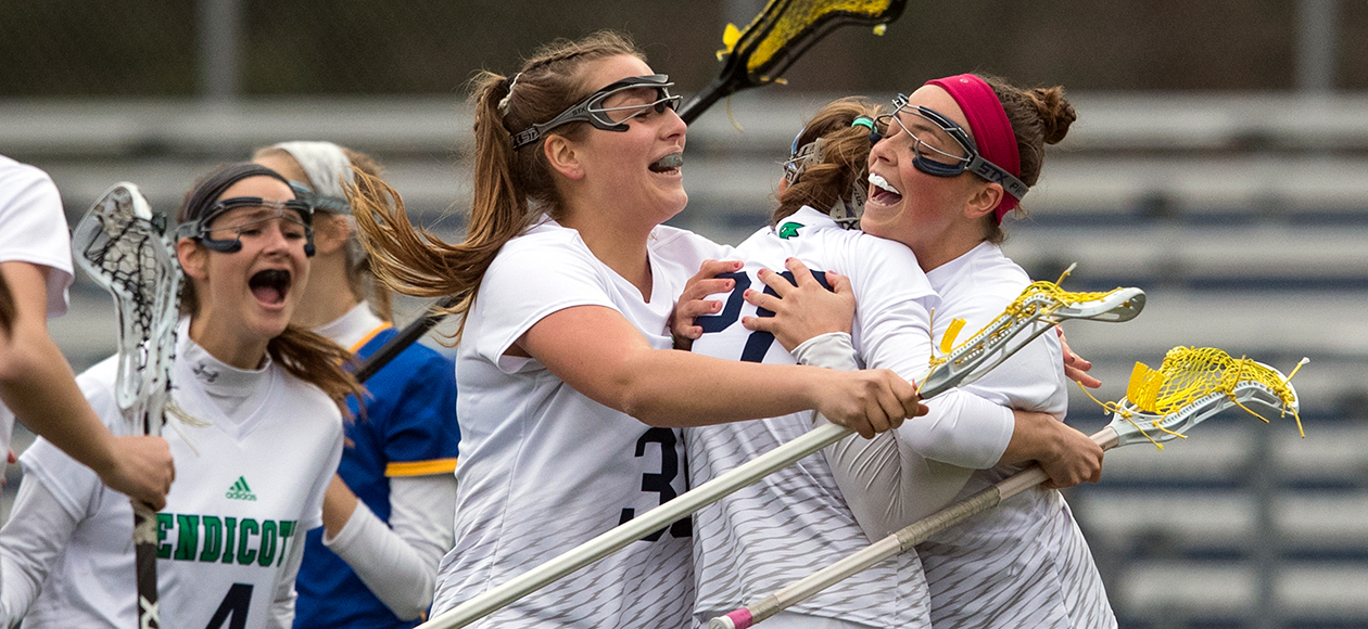 Members of the Endicott women's lacrosse team hug after a goal.