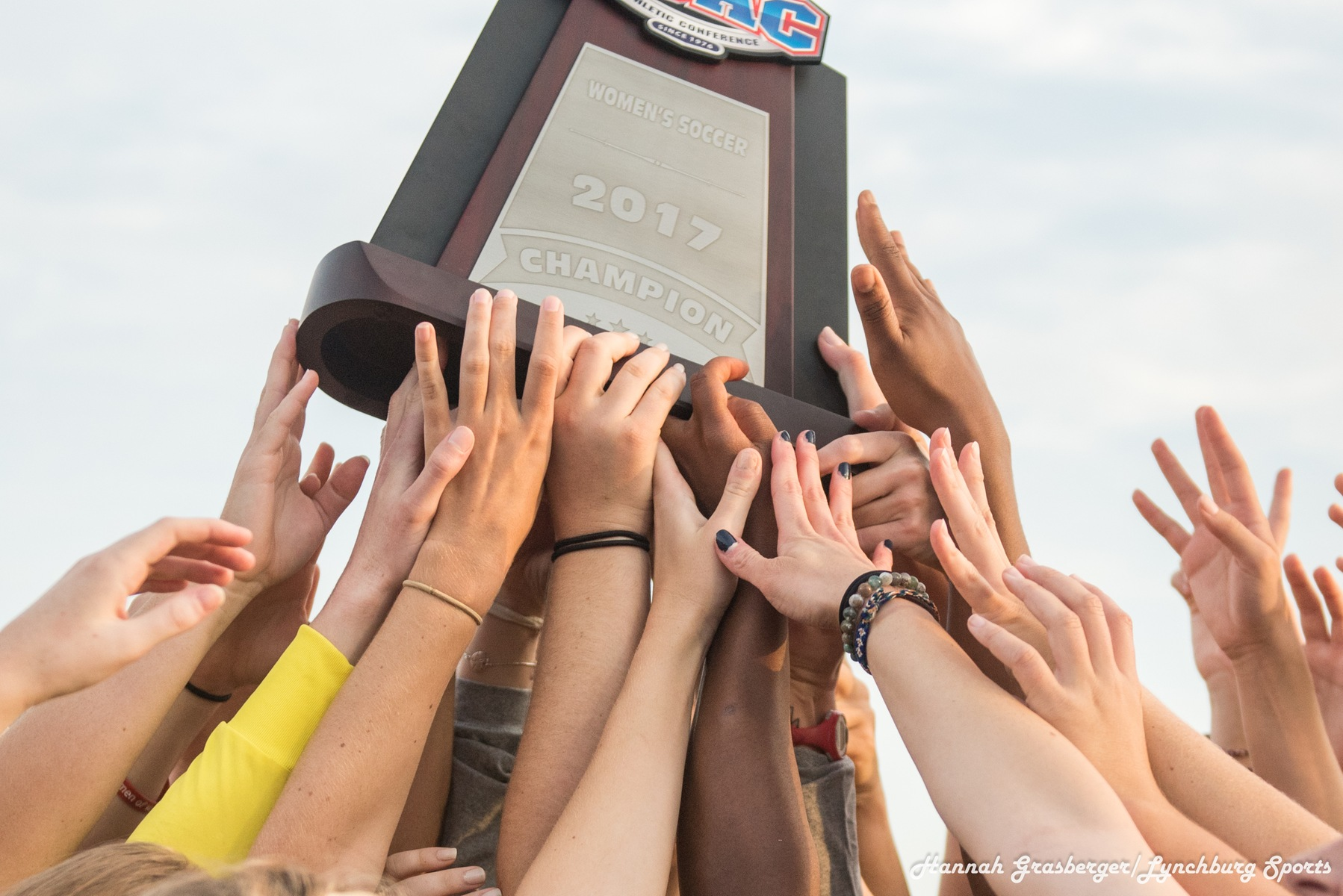Hands lift up the 2017 ODAC women's soccer championship trophy