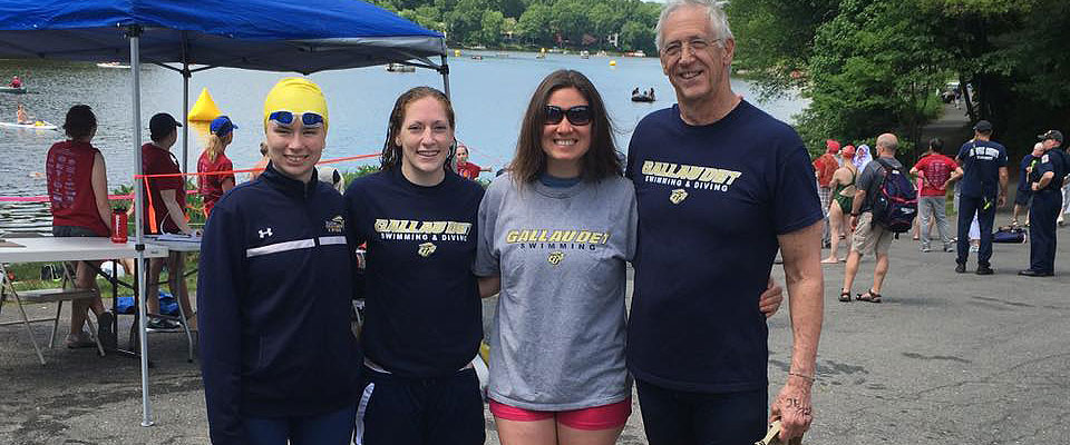 Pictured left to right: Faye Frez-Albrecht in yellow swim cap, Katie Giles in navy t-shirt, Stephanie Danner in gray t-shirt, head coach Larry Curran in blue t-shirt in front of lake.