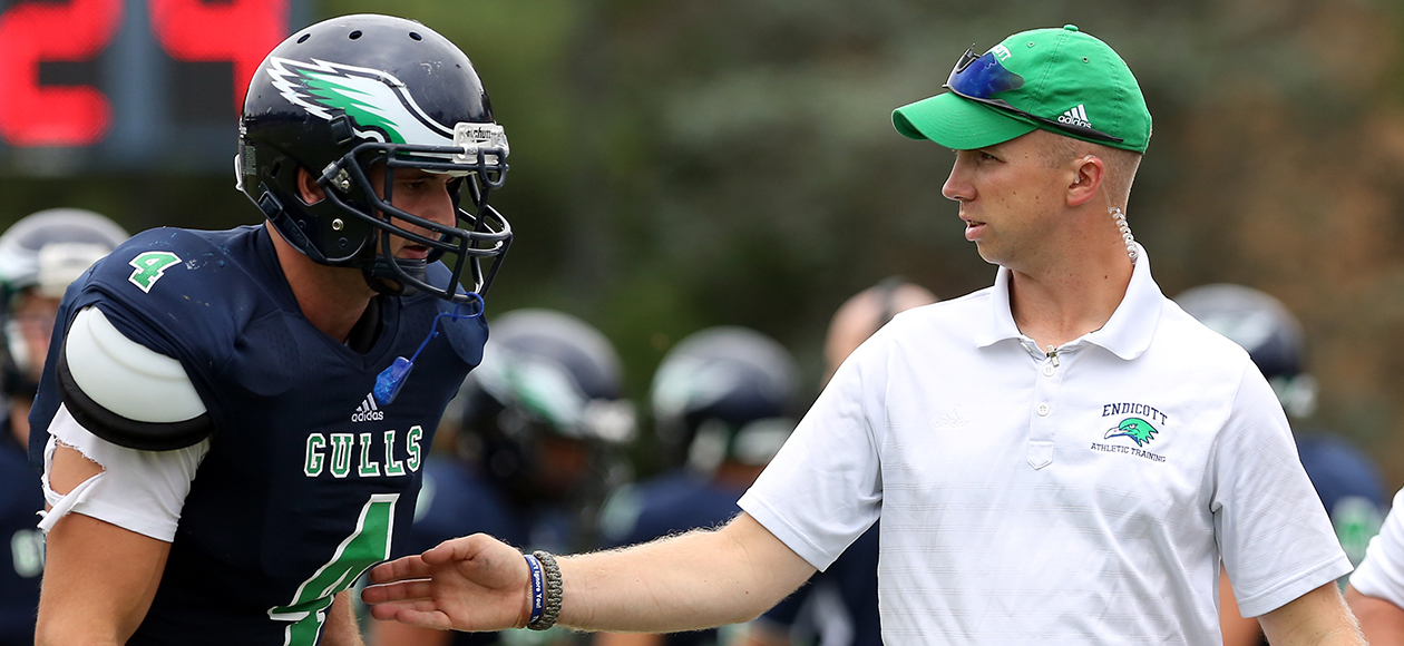 Endicott head athletic trainer James Daley stands on the sidelines and reaches out with his right arm to touch an Endicott football player, number 4, Jacob Simons.