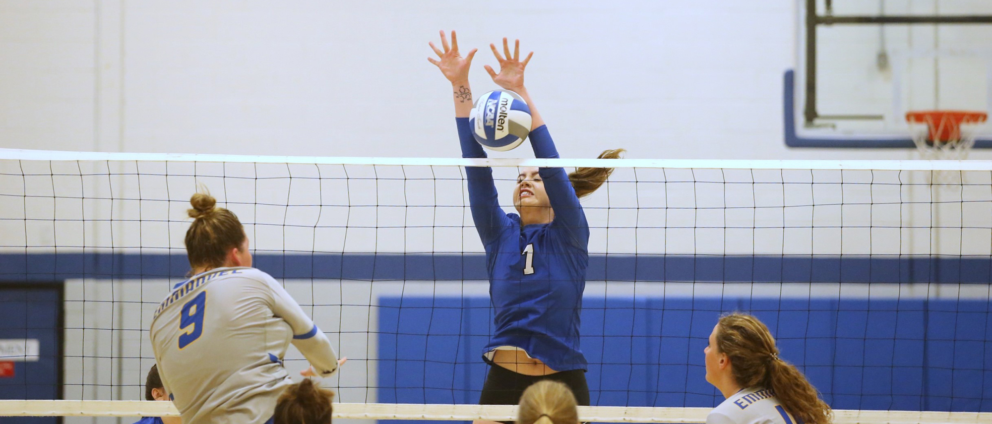 Becker volleyball's junior Gillian Criddle goes up for a block against Emmanuel College