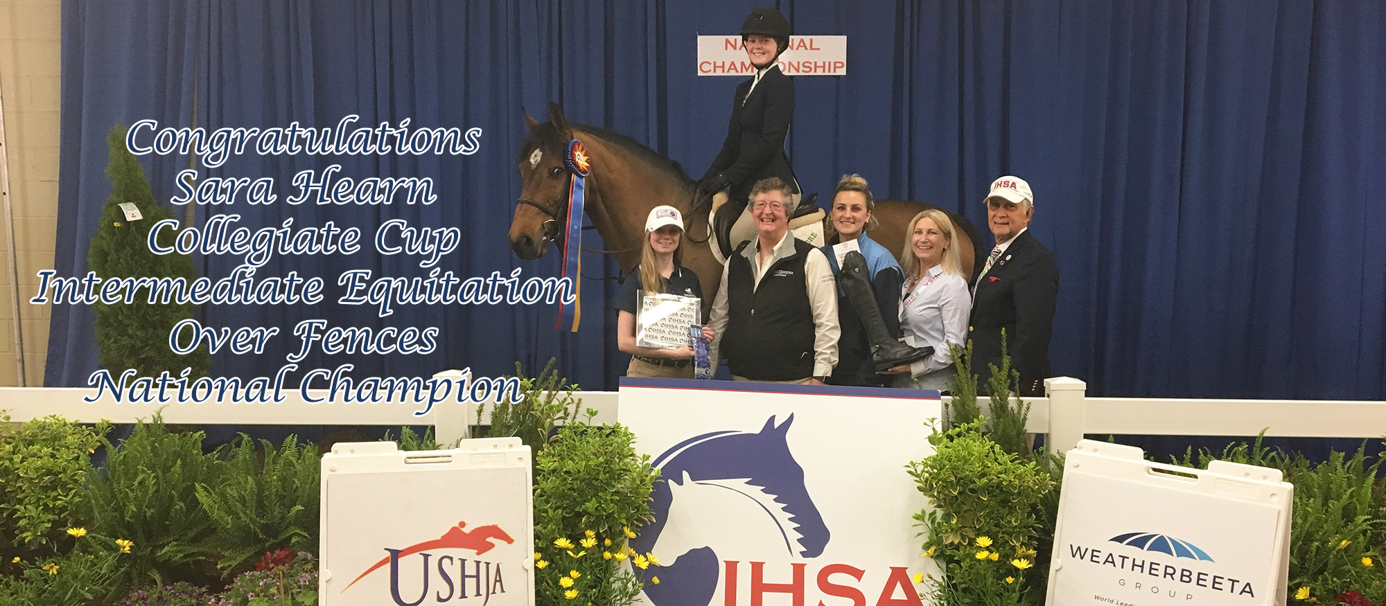 Photo showing Lyons first year rider Sara Hearn, who won the 2018 IHSA Collegiate Cup Intermediate Over Fences Equitation. She is pictured on the winning horse, along with head coach CJ Law, assistant coach Tara Matthews and IHSA Executive Director, Bob Cacchione.