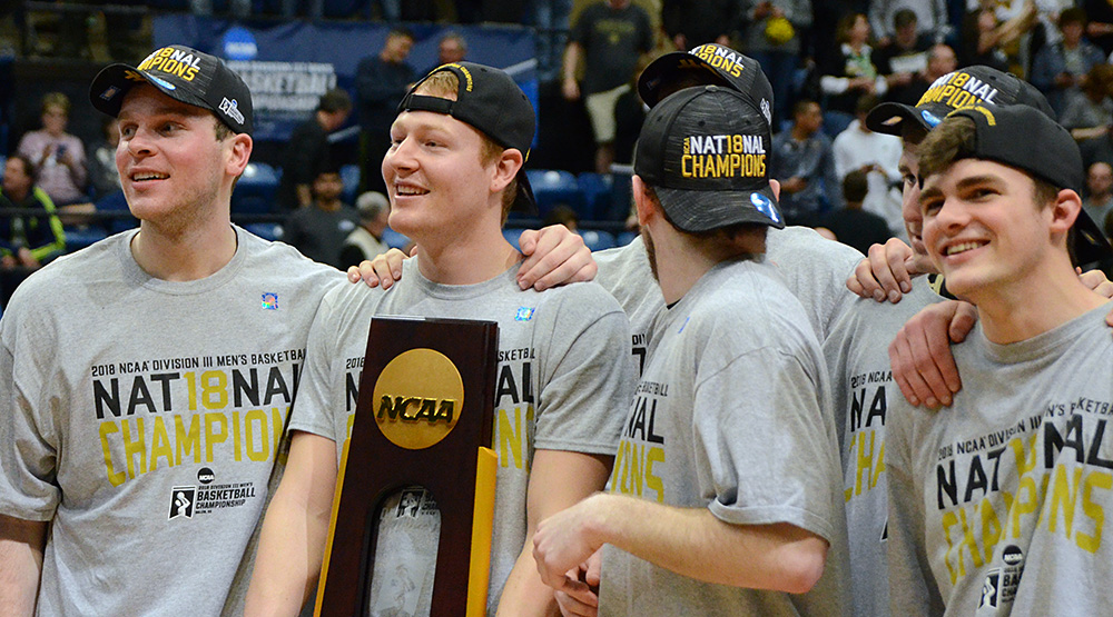 Nebraska Wesleyan players hold the Division III men's basketball national championship trophy after the Prairie Wolves' win vs. UW-Oshkosh in Salem. (Photo by Dave Hilbert, d3photography.com)