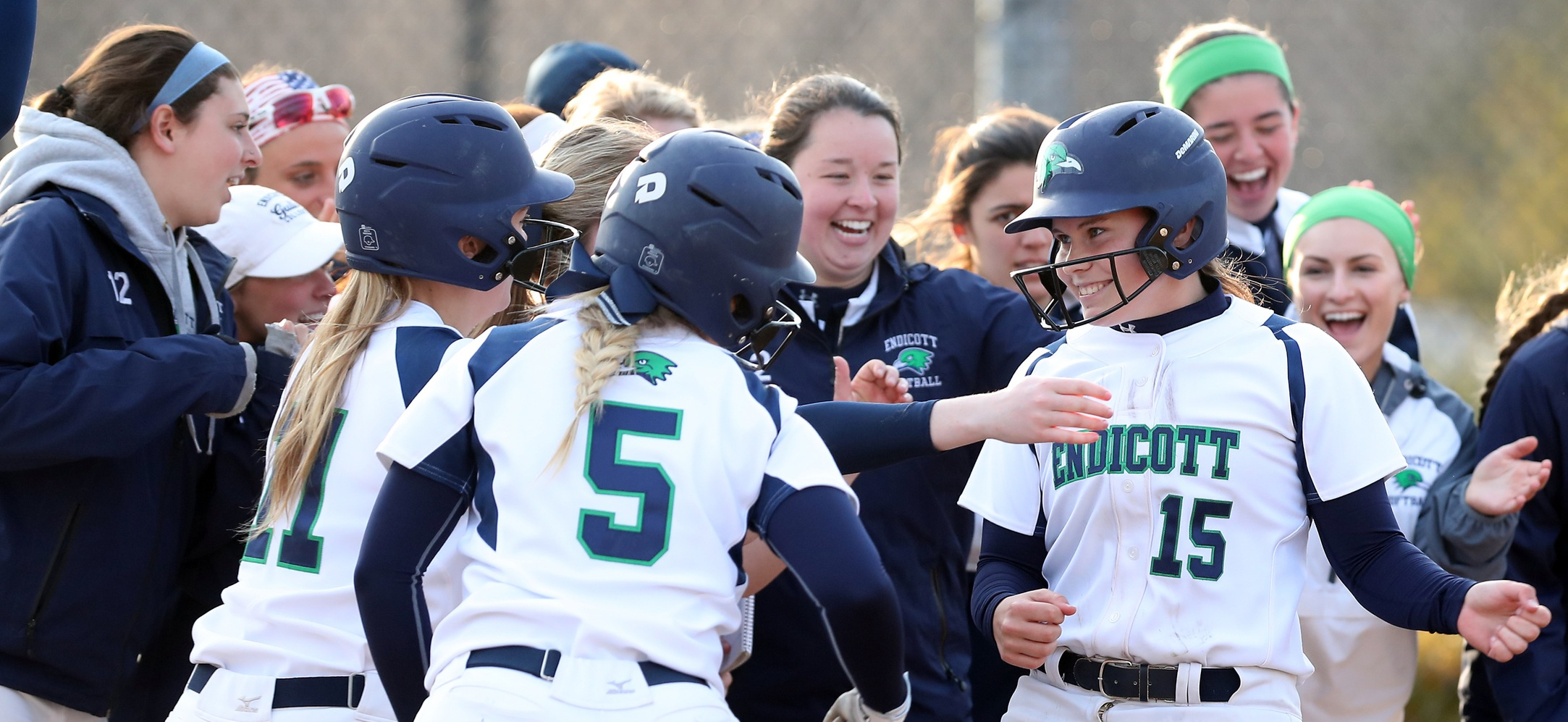 Members of the Endicott softball team celebrate a run.