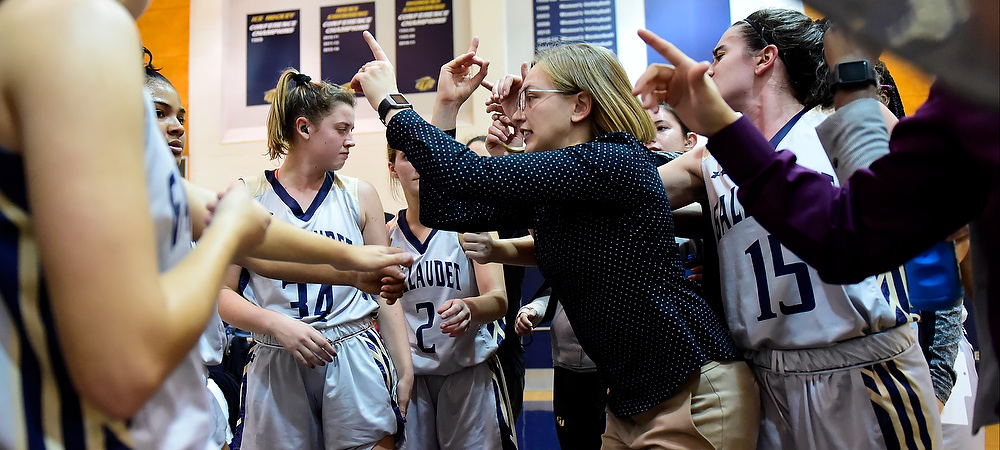 Gallaudet women's basketball coach Stephanie Stevens coaches up her team during a timeout in the huddle.