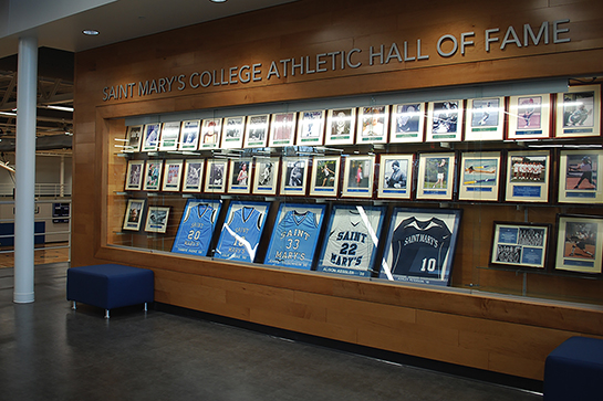 A wood, built-into-the-wall display case shows the Hall of Fame plaques as well as retired jerseys inside Angela Athletic & Wellness Complex.