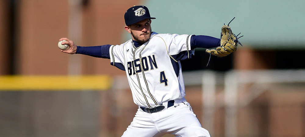 Gallaudet's Robersy Delgado starts his pitch with the ball in his hand wearing his white uniform, reading BISON in navy blue letters across.
