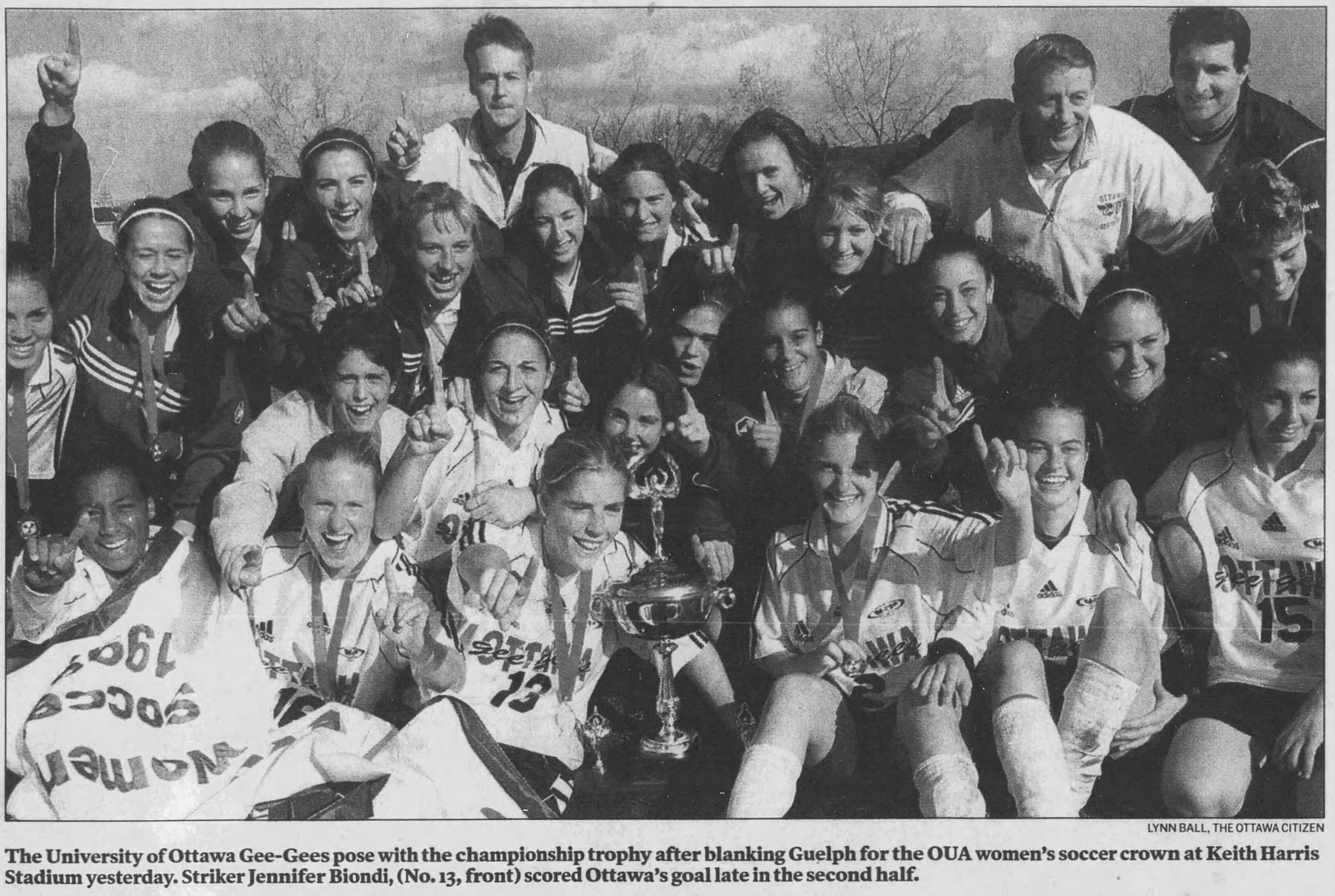 Black and white photo of team celebrating with trophy and banner.