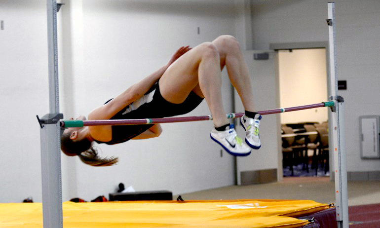Junior Anna Skow-Anderson arches over the bar in the high jump of the MIAC pentathlon. She finished second in the event.