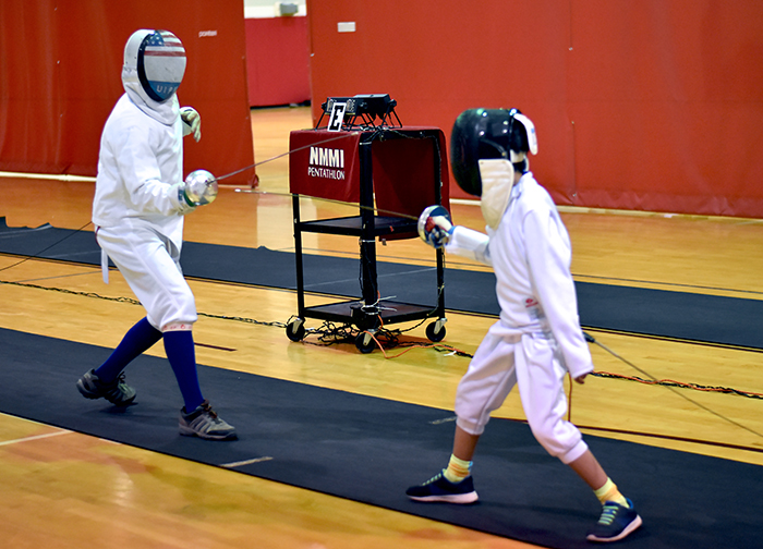 Roswell septuagenarian Dave Sourk (left) crosses sabers with Lukas, the pre-teen son of NMMI professor Aonan Tang, at the 2018 Christmas Classic Fencing Tournament.