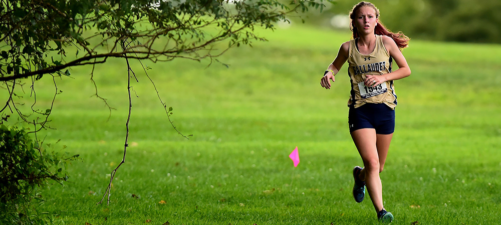 Sierra Pratt runs through an outdoor cross country course. She runs around a tree and some branches.
