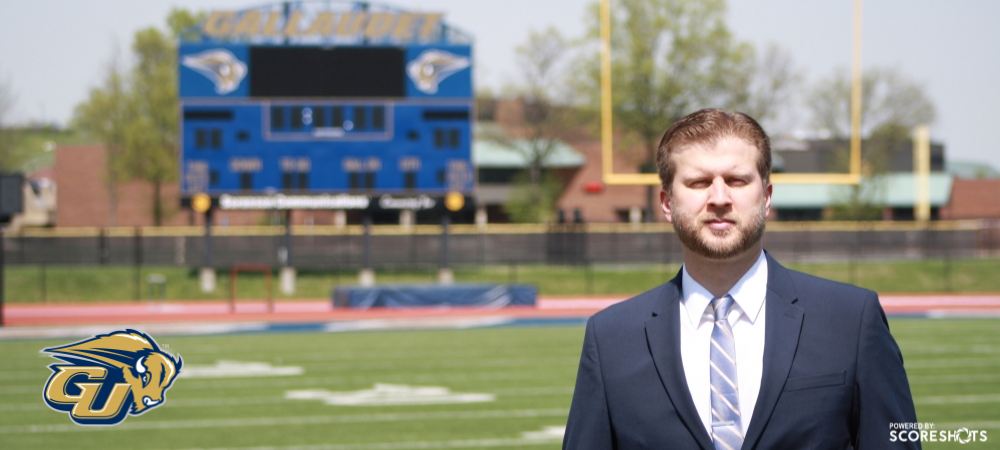 Gallaudet Athletic Director Victor Mansure stands on Hotchkiss Field and looks towards the camera on a sunny day. The Gallaudet scoreboard is in the background. A GU Bison logo is in the lower left hand corner.