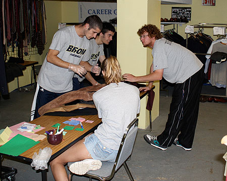 Gallaudet student-athletes organize and sort business clothes at STRIVE DC