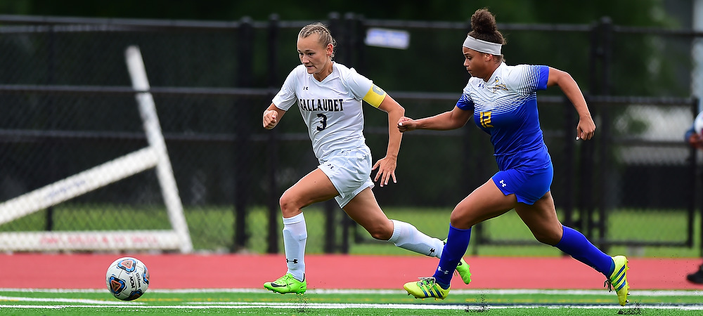Gallaudet's Sabina Shysh runs past a defender on the soccer field as she chases after the soccer ball.