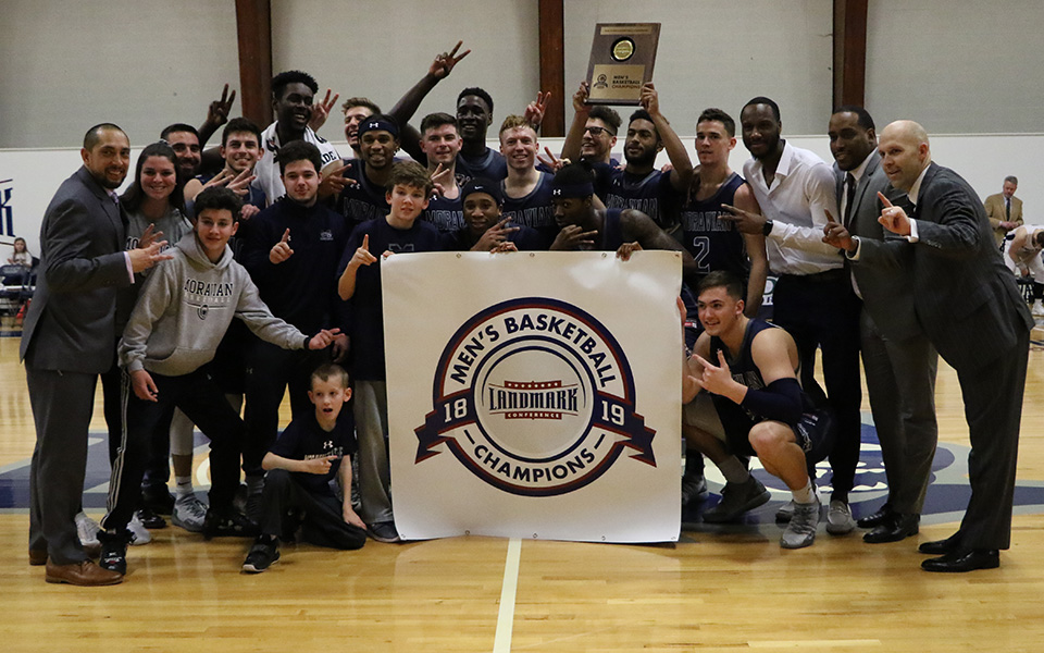 The Greyhounds with the 2019 Landmark Conference Championship banner and plaque after an 86-72 victory at Drew University.
