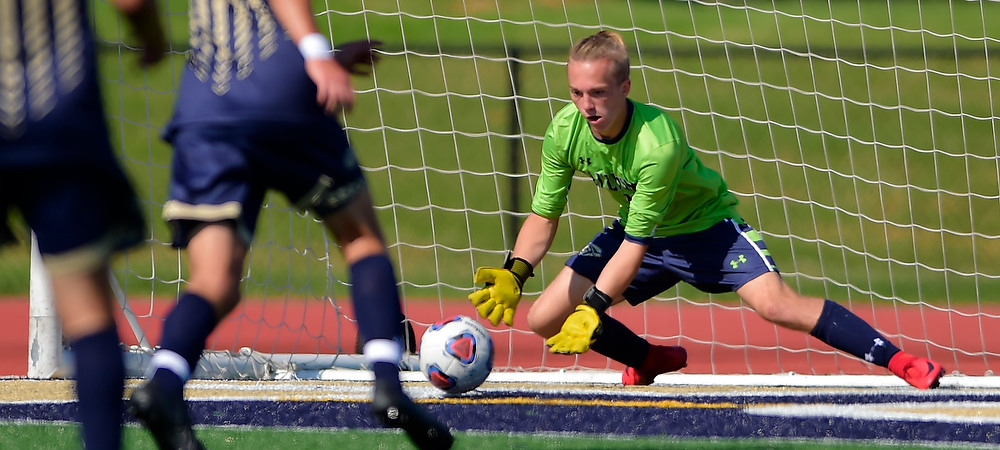 Shane Angel makes a save for the Bison in a day soccer game on a turf field.
