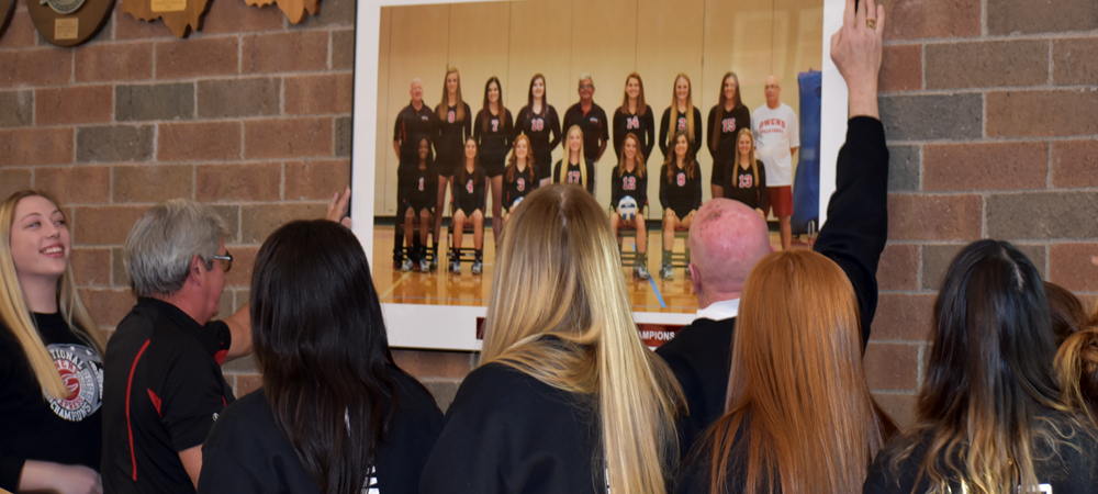 Head Coach Sonny Lewis and assistant Denny Caldwell unveil a team portrait in honoring the team's Division III National Championship. The photo is displayed across from the doors to the main gym in the SHAC.