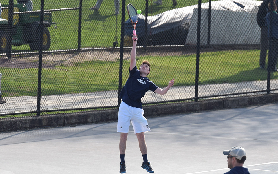 Senior Peter Demyan serves during singles action versus Neumann University at Hoffman Courts.