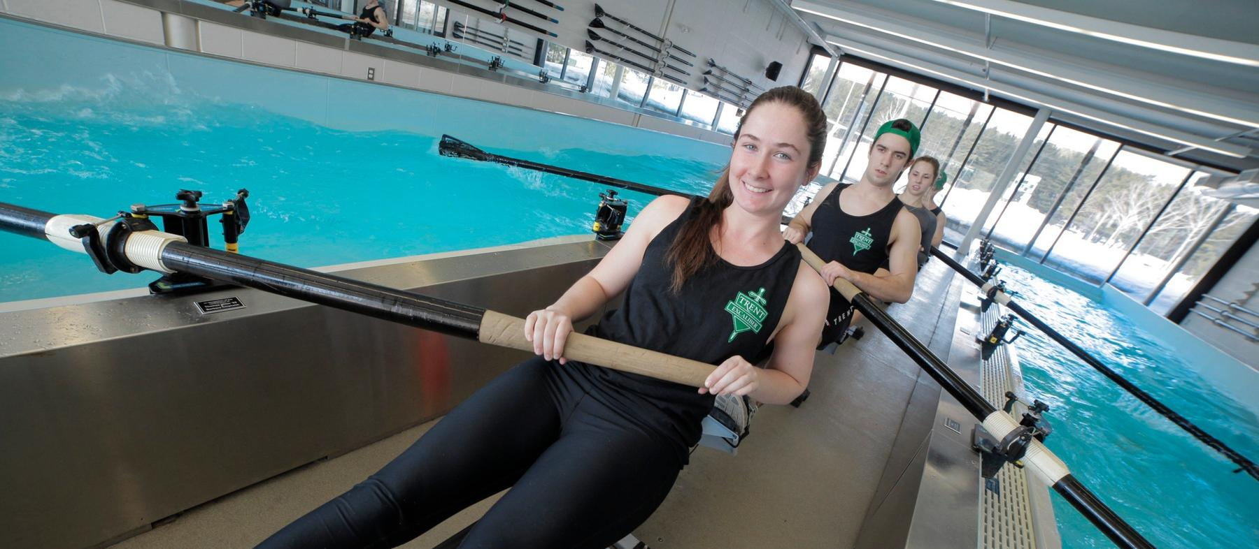 A group of varsity athletes row in the indoor rowing tank at Trent University.