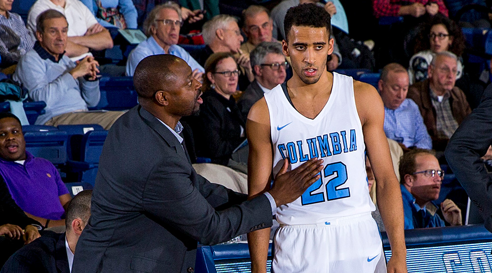 Jean Bain talks with a Columbia basketball player during a Columbia home men's basketball game.