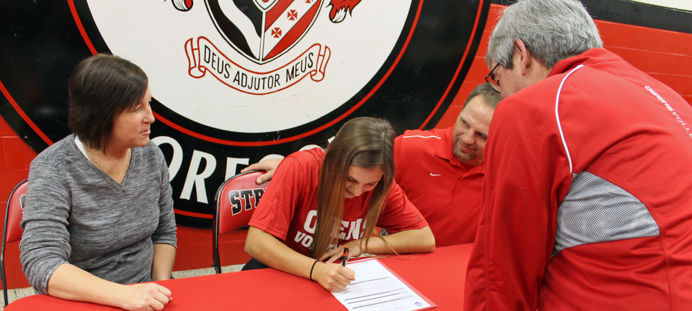 Cassidy Wlodarz signs her LOI as her parents and Owens volleyball head coach Sonny Lewis look on. Photo by Nicholas Huenefeld/Owens Sports Information